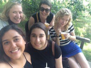photo of five women on bench enjoying water ice